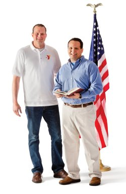 Photo of men holding a history book in front the American flag.
