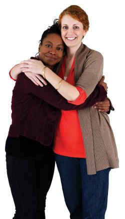 A photo of two women hugging and smiling.